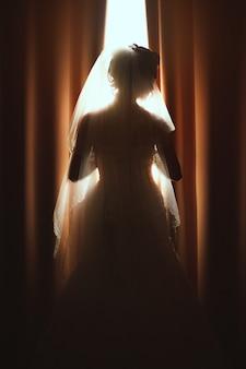 Hermosa novia de pie junto a la ventana. la chica en un vestido de novia blanco.