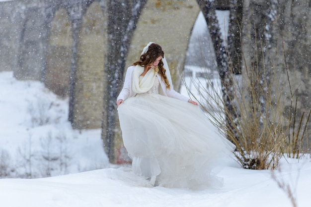 Hermosa novia posando cerca de un viejo puente de acueducto abandonado. la novia admira su vestido