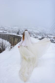 Hermosa novia posando en un viejo puente de acueducto abandonado. la novia se para con la espalda.