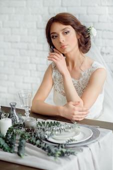 Hermosa novia con ramo de flores. morena en una pared de ladrillo blanco leonado