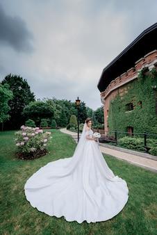 Hermosa novia con ramo de novia y vestido de novia de lujo está de pie delante de un edificio cubierto de hojas verdes