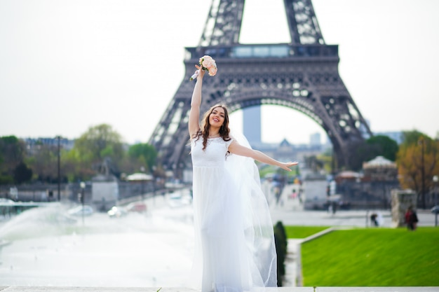 Hermosa novia en rico vestido de novia gira en la plaza ante la torre eiffel