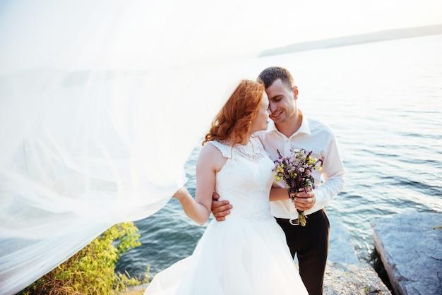 Hermosa novia rubia y novio con clase en las rocas, en medio del mar