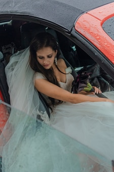 La hermosa novia está sentada en un coche rojo con un vestido blanco y un ramo de flores. concepto de boda