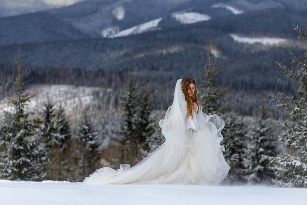Hermosa novia sobre un fondo de montañas cubiertas de nieve.
