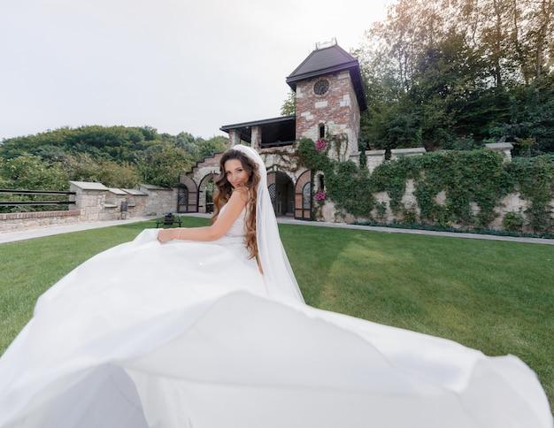 Hermosa novia sonriente con un vestido de lujo en el patio de césped del antiguo edificio,