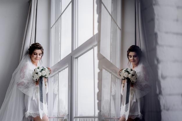 Hermosa novia vestida con ropa de dormir de seda y velo sostiene ramo de novia hecho de peonías blancas cerca de la ventana enorme