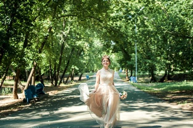 Hermosa novia con un vestido beige con una falda caminando en el parque