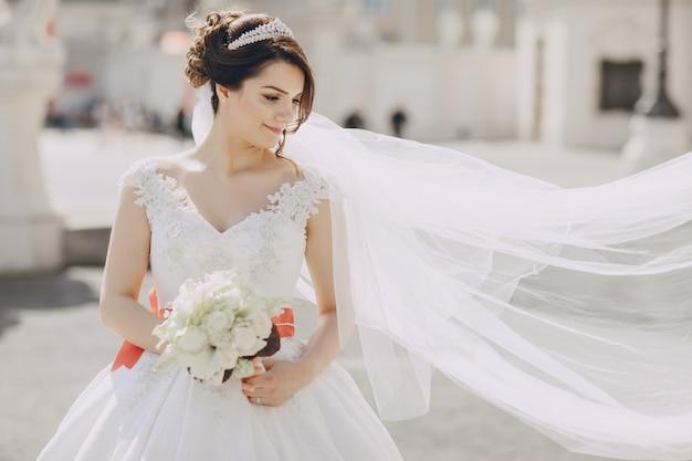 Hermosa novia con un vestido blanco y una corona en la cabeza en un parque y con ramo
