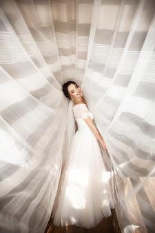 Hermosa novia en vestido blanco posando bajo la cortina