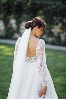 Hermosa novia en vestido blanco posando