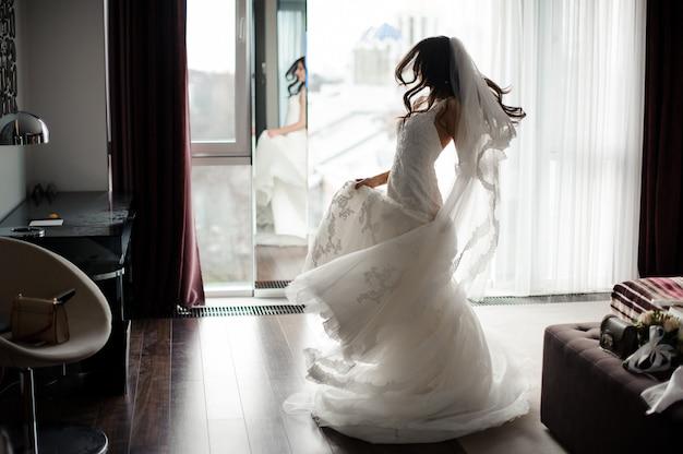 Hermosa novia con vestido blanco y velo bailando cerca de la ventana