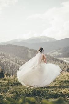 Una hermosa novia con un vestido de novia gira en las montañas. foto vertical. vista trasera.