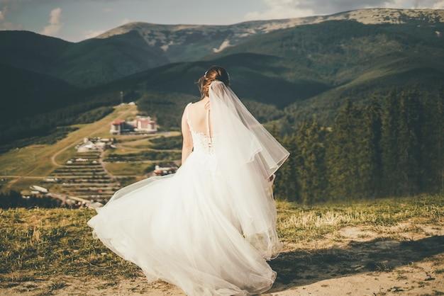 Una hermosa novia con un vestido de novia gira en las montañas. vista trasera. foto de alta calidad