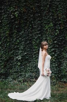 Hermosa novia en vestido de novia de moda sobre fondo natural. la impresionante joven novia es increíblemente feliz. día de la boda. un hermoso retrato de novia.