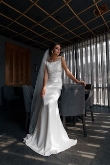 Hermosa novia en vestido de novia de moda con velo largo interior.