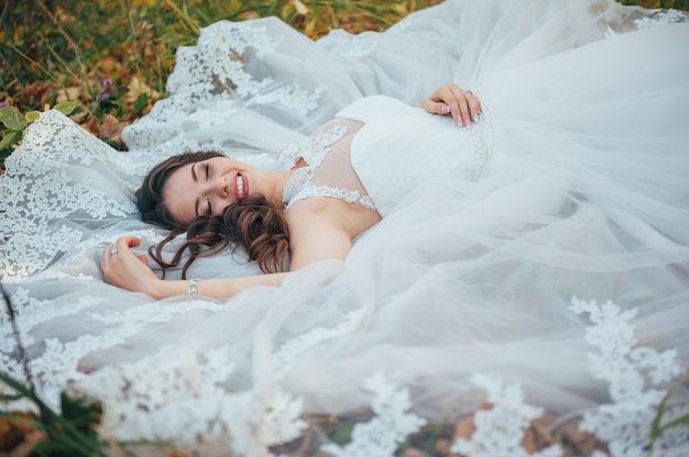 Hermosa novia en un vestido de novia en el parque de otoño