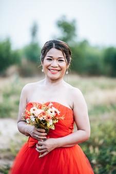 Hermosa novia en vestido de novia de publicación en la naturaleza