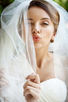 Hermosa novia en vestido de novia y velo guiño, enviando beso.