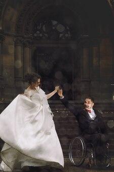 Hermosa novia y el novio en la silla de ruedas bailan antes de la antigua iglesia católica