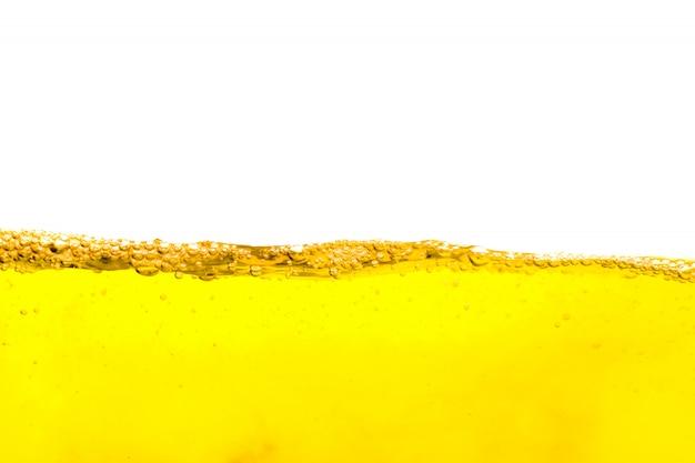 Hermosa ola de burbuja de aire en el interior aislado sobre fondo blanco, bebida de verano amarilla con burbujas, burbujas de cerveza