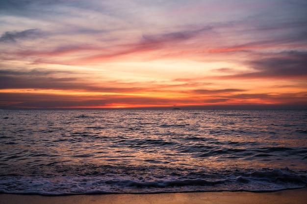 Hermosa ola de mar tropical y cielo colorido al atardecer