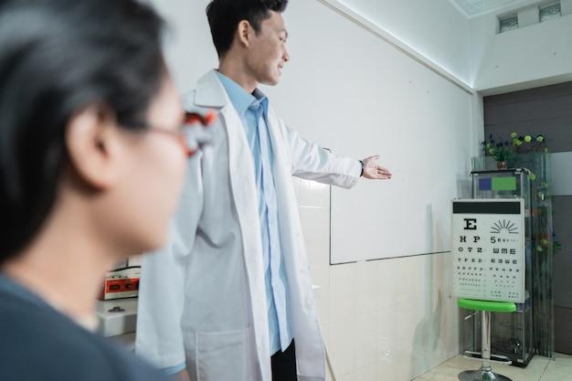 Una hermosa paciente está haciendo una prueba ocular siguiendo las instrucciones de un médico que está de guardia en una habitación en la clínica oftalmológica.