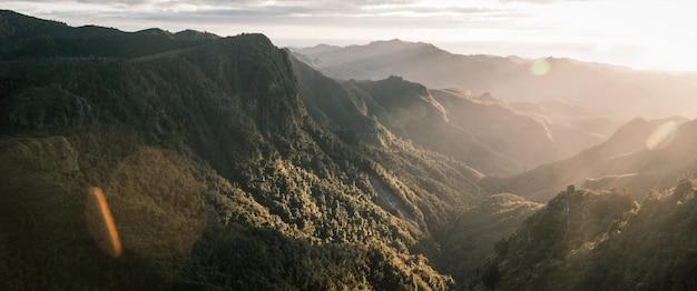Hermosa panorámica de montañas y acantilados rocosos y niebla natural