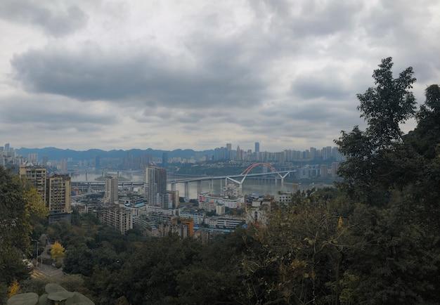 Hermosa panorámica de yuzhong qu, china con cielo nublado y vegetación en primer plano