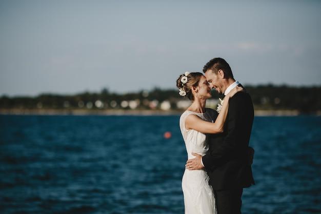 Hermosa pareja se abraza tiernamente de pie en la orilla del lago