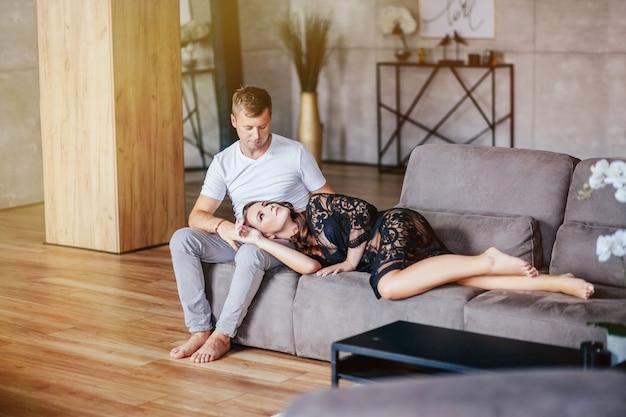 Hermosa pareja abrazándose y mirándose en casa en el sofá