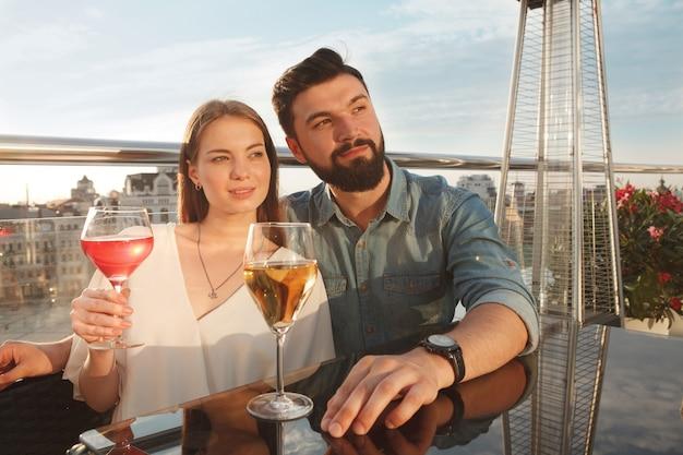 Hermosa pareja abrazándose en la terraza del bar, bebiendo vino al atardecer, celebrando el aniversario
