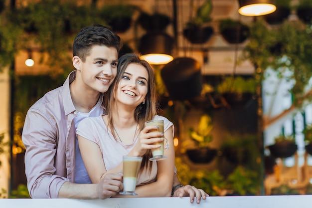 Hermosa pareja abrazándose en la terraza de verano del restaurante