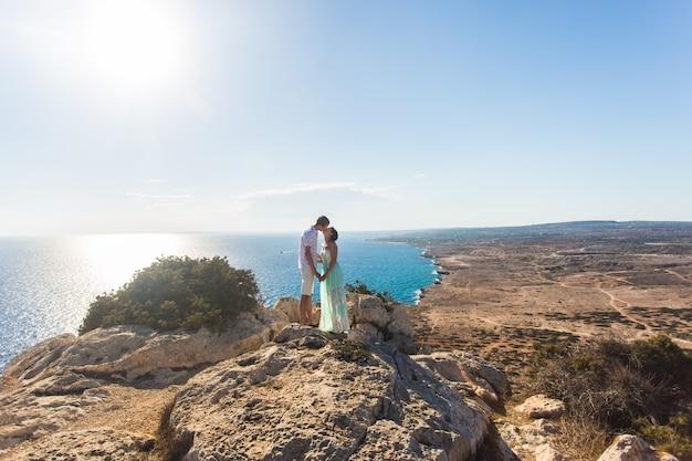 Hermosa pareja abrazo sobre piedras y fondo del mar