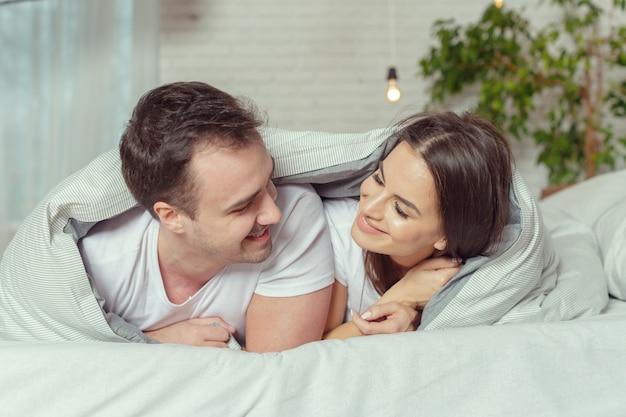 Hermosa pareja acostada en la cama