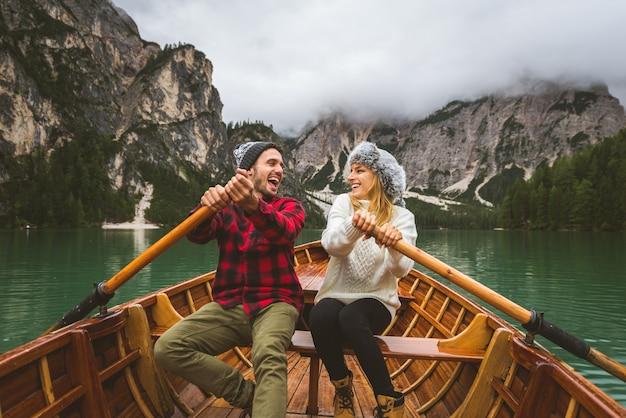 Hermosa pareja de adultos jóvenes visitando un lago alpino en braies italia