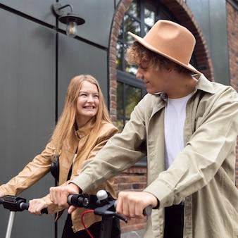 Hermosa pareja al aire libre en la ciudad con scooters eléctricos