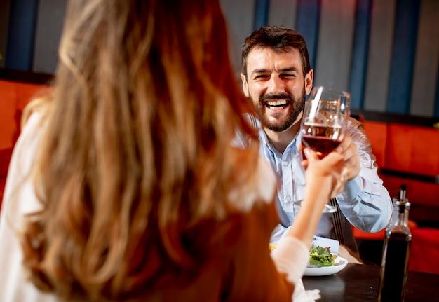 Hermosa pareja amorosa pasa tiempo juntos y brinda por los vasos en un restaurante moderno