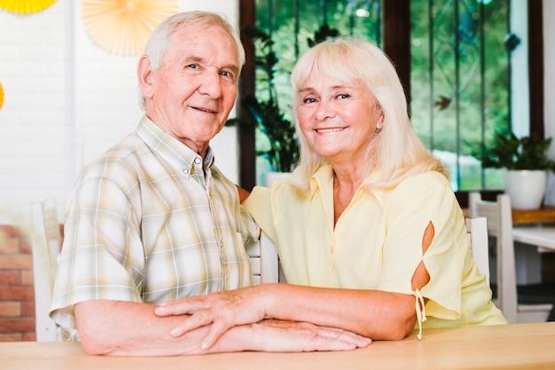 Hermosa pareja de ancianos acurrucarse y mirando a cámara