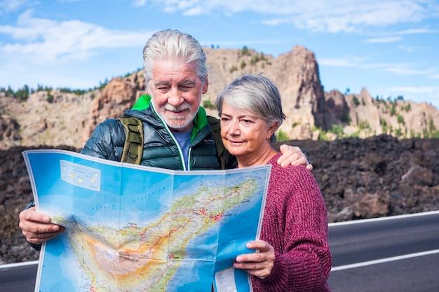 Hermosa pareja de ancianos caucásicos, hombre y mujer, personas que viajan usando un mapa de papel de estilo antiguo en la montaña: disfruten del estilo de vida y la vida jubilada junto con una mochila y las necesidades de una aventura