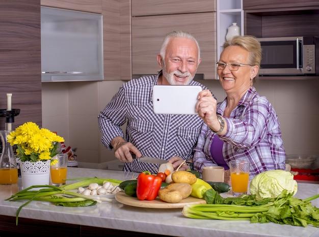 Hermosa pareja de ancianos cocinando en la cocina con los demás y viendo algo en el dispositivo