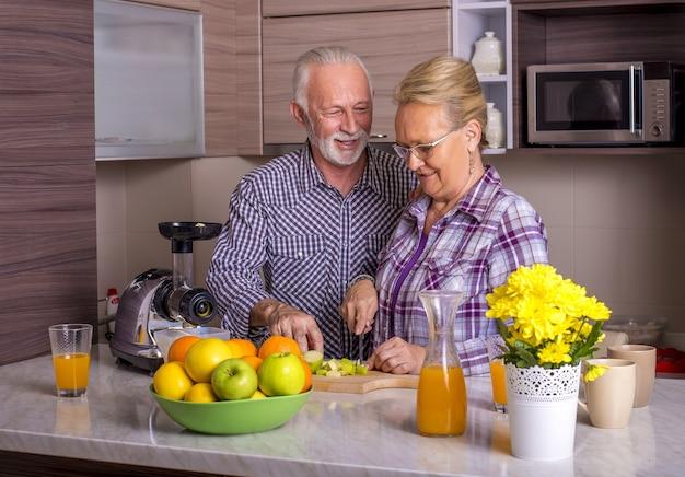 Hermosa pareja de ancianos cocinando en la cocina con los demás
