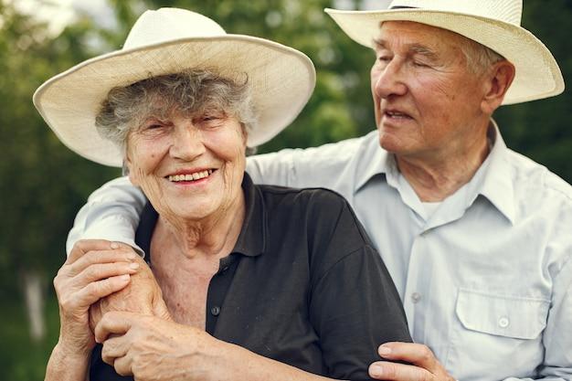 Hermosa pareja de ancianos pasar tiempo en un jardín de verano