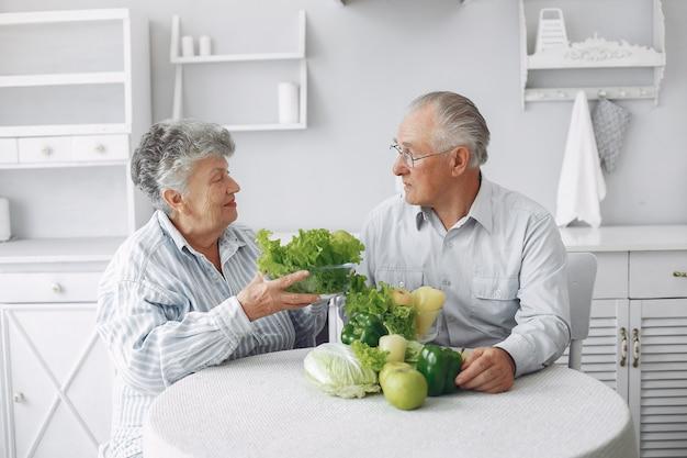 Hermosa pareja de ancianos prepara la comida en la cocina