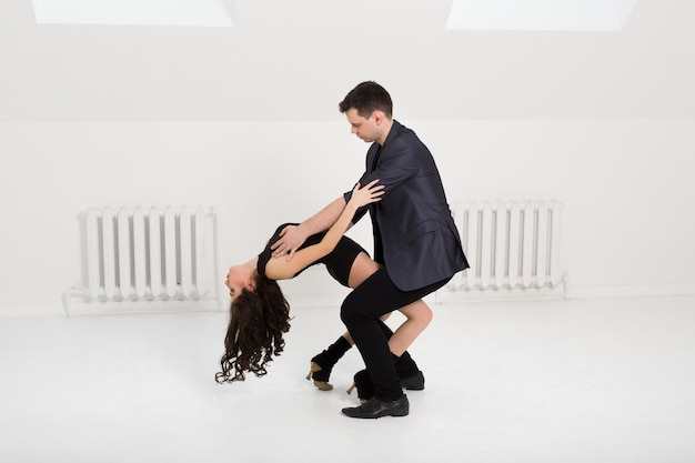 Hermosa pareja bailando bachata en pared blanca