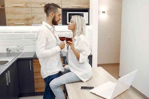 Hermosa pareja bebe vino tinto en la cocina
