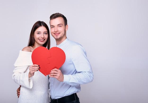 Hermosa pareja blanca con un corazón rojo sonriendo, de pie en el fondo.