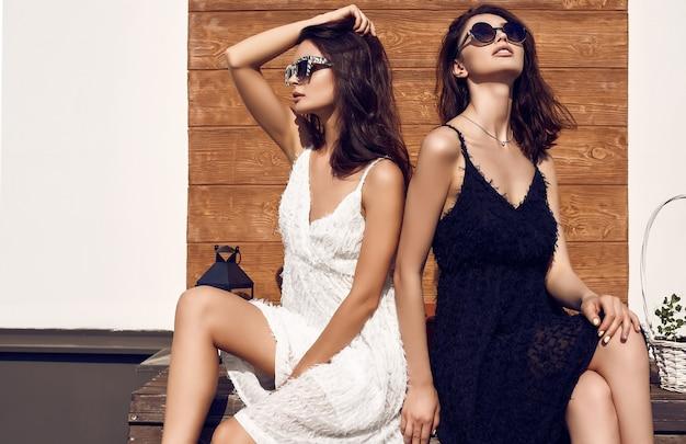 Hermosa pareja brillante de mujeres morenas en vestidos blancos y negros