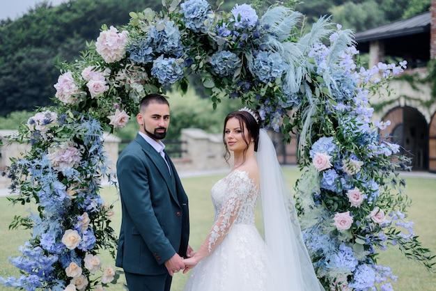 Hermosa pareja caucásica está de pie delante de decorado con arco de hortensias azules y tomados de la mano juntos