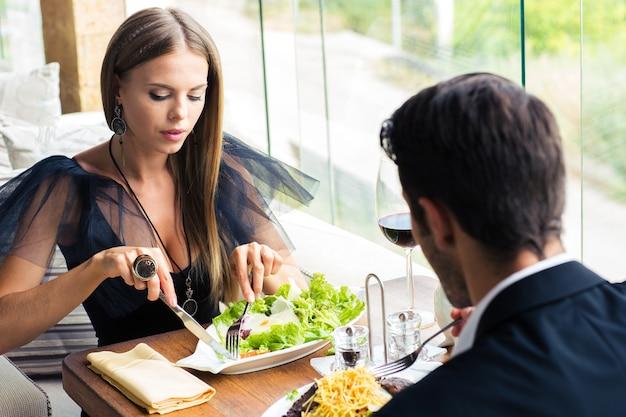 Hermosa pareja comiendo en restaurante